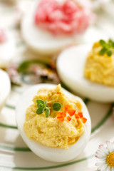 Deviled egg topped with fresh herbs and habanero pepper
