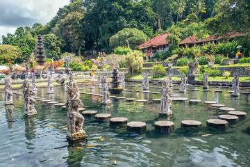 Water Palace of Tirta Gangga - famous landmark of Bali island, Karangasem, Indonesia. Popular beautiful water palace with fountains and traditional hindu demons statues, travel landscape photography