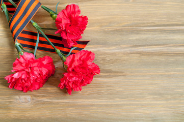 9 May background - red carnations and George ribbon lying on the wooden background