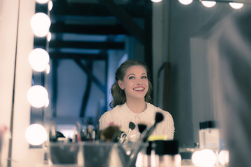 Smiling pretty young woman retro 1940s style looking in theater mirror.