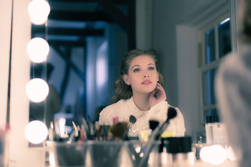 Dreamy pretty young woman retro 1940s style looking in theater mirror.
