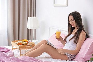 Beautiful young woman having breakfast and reading magazine while sitting on bed at home