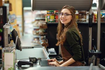Cheerful cashier woman on workspace in supermarket shop.