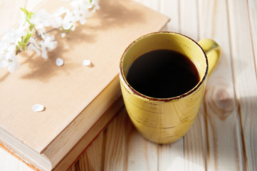 old book, cup of coffee next to spring white flowers on wooden texture