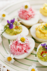 Deviled eggs with various fillings decorated with fresh herbs and edible flowers