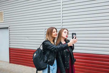 Two young girls taking selfie using smartphone
