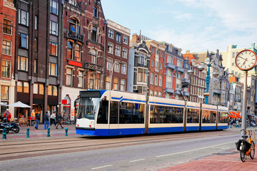 Poster Amsterdam Public tram crossing Damrak main street crowded with tourists Amsterdam