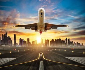Poster Avion à Moteur Landing commercial airplane at the runway, modern city on background