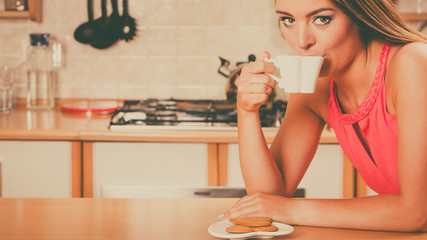 Woman with gingerbread cookies drinking tea coffee