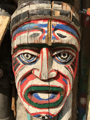 Authentic painted wooden totem pole in an African village. Original sculpture in wood. Wood tribal sculpture, colored portrait.