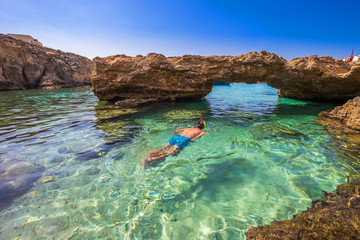 Blue Lagoon, Malta - Snorkeling tourist at the caves of the Blue Lagoon on the island of Comino on a bright sunny summer day with blue sky Wall mural