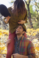 Young woman playfully sitting on her boyfriend's shoulders