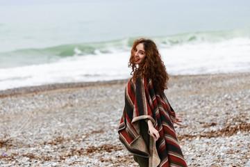 Portrait of happy brunette woman on the beach wearing poncho