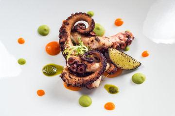 close up of cooked octopus on a white plate