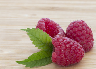 Ripe sweet raspberries on wooden table