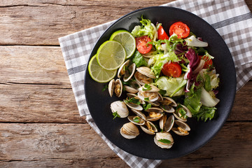 Fresh clams with lime and greens and mix salad close-up. horizontal top view