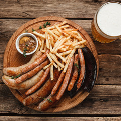 Mug with cold tasty beer and delicious grilled sausages with french fries served with delicious sauce, close up view. German pub menu photo.