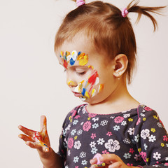 Colorful painted hands in a beautiful young girl (art, childhood, colour concept)