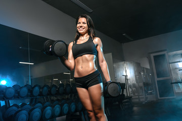 athletic woman pumping up muscles, training workout with dumbbells in gym