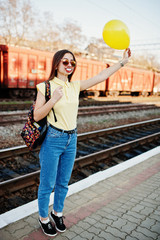 Young teenage girl standing on the platform at the train station with funny lips on stick and balloon at hand, wear on yellow t-shirt, jeans and sunglasses, with backpack.