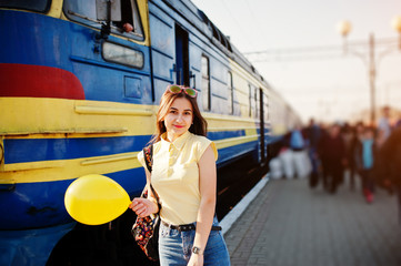Young teenage girl standing on the platform at the train station with balloon at hand, wear on yellow t-shirt, jeans and sunglasses, with backpack.
