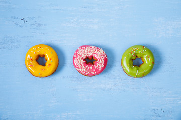 Donuts with icing. Sweet glazed donut. Dessert with sprinkles. On blue wooden rustic background.
