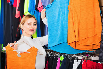 Cheerful  girl choosing a t-shirt in the store