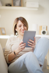 Young Caucasian woman using tablet computer and sitting on sofa at personal work space