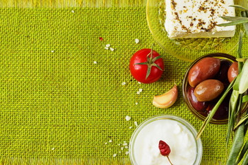 Green cloth background with the space for a text. Traditional Mediterranean motive - feta cheese, tzatziki, olives, garlic,jar with olive oil, tomato, beetroot, tomato, white dry wine. Healthy food