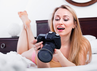 Laughing woman lying in the bed and holding a camera