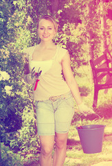 female gardener with working tools outdoors.