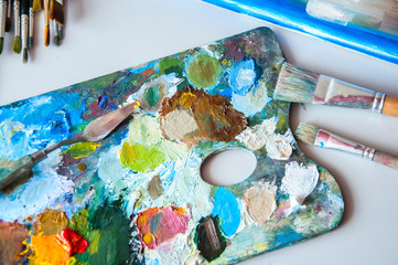 Art brushes and palette with oil paints on a table. Painting concept.