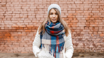 Beautiful stylish girl in a warm hat, a white jacket and a fashionable scarf near the wall