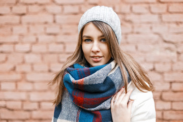 Portrait of a young girl in a knitted hat, a white jacket and a bright scarf near a brick wall