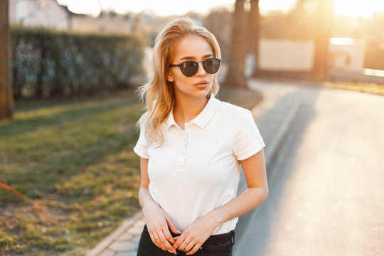 Young girl in trendy sunglasses and white polo shirt in a spring day at sunset