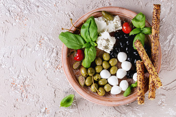 Mediterranean appetizer antipasti plate with green black olives, feta cheese, mozzarella, capers, pepper, basil with grissini bread sticks over beige concrete texture background. Top view with space