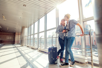Traveling couple standing in airport terminal.