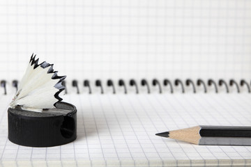 An old, second-hand, sharpener with a shavings and a simple pencil lie on the notebook in a box. Selective focus. Close-up
