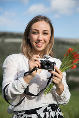 A young woman with a camera and a bouquet of poppies