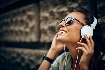 Photo sur Plexiglas Magasin de musique Happy young woman listening to music via headphones on the street on a sunny day