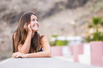 Portrait of smiling woman with leaning on a wall