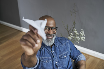 Mature man plying with paper plane