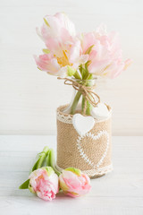 Pink tulips in rustic bottle