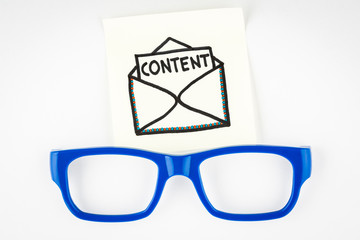 Email content marketing concept with blue eyeglasses on white background