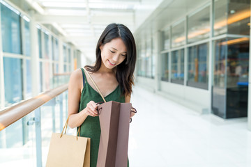 Woman open the paper bag in shopping mall