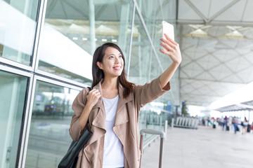 Woman taking selfie by mobile phone in hong kong international airport