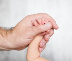 Newborn baby hand in father's hand