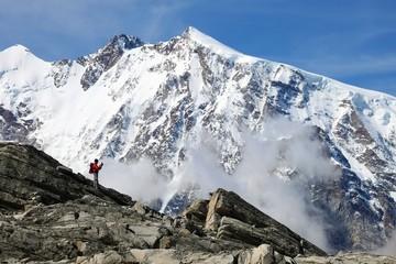 Hiker taking a picture in front of Monte Rosa, near Passo di Monte Moro, Province of Verbano Cusio Ossola, Piemonte, Italy