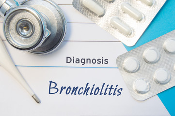 Diagnosis Bronchiolitis. Doctor's stethoscope, electronic thermometer and two blisters of pills lying near pad with inscription of diagnosis Bronchiolitis. Concept of report in internal medicine