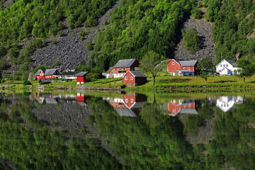 Perfect reflection of some typical norvegia houses into a lake in late spring, Odda, Hardaland, Norway